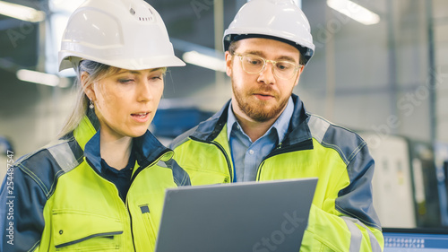 Obraz Male and Female Industrial Engineers Work on a Manufacturing Plant, They Discuss Project, Point in the Direction of the Machinery while Using Laptop.  - fototapety do salonu