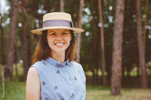 Photo Joyful woman in straw boater hat smile on nature in summer