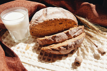 Loaf Of Bread With Milk Or Yogurt On Table