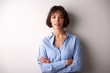 Attractive businesswoman with folded arms standing at isolated background