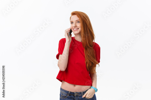 Fototapeta Cheerful young woman talking on mobile phone isolated on gray background. obraz
