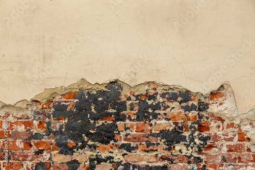 An old damaged brick wall partially covered with old cracked plasterwork Canvas-taulu