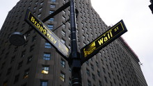 Person Showing Wall Street Sign