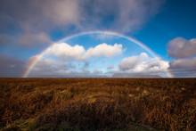 White Clouds And Rainbow Photo On Horizon