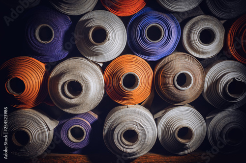 Fotografiet  many textile rolls of blue, white and orange colors stacked one over the other i