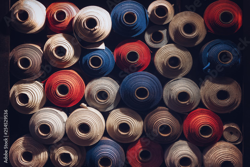 many textile rolls of blue, white and orange colors stacked one over the other in dark light