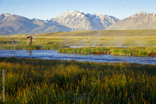 One man fly fishing on the Owens River at sunrise with the Sierra Nevada Mountai Fototapet