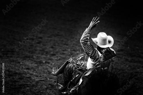 Fotografía  Monochrome rodeo cowboy in a white hat riding a bronco in ththe spotlight