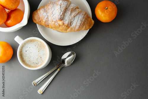 Fotografie, Obraz  Delicious breakfast coffee with croissant and citrus fruits - oranges