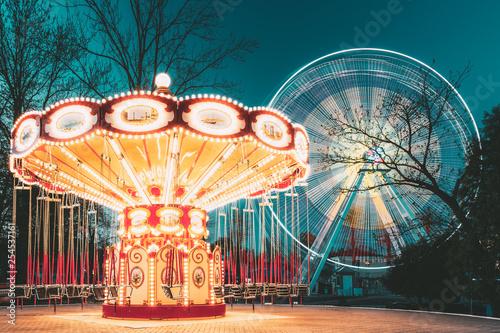 Foto auf Leinwand Vergnugungspark Illuminated Attraction Ferris Wheel And Carousel Merry-go-round On Summer Evening In City Amusement Park.