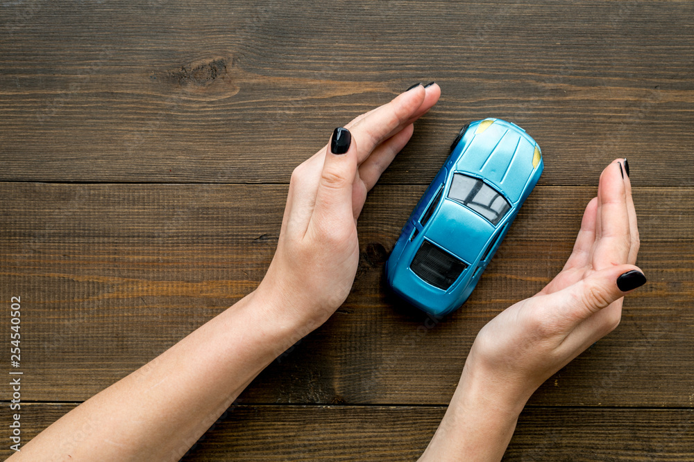 Fototapety, obrazy: Car insurance concept. Safety of auto. Car toy in female hands on dark wooden background top view space for text