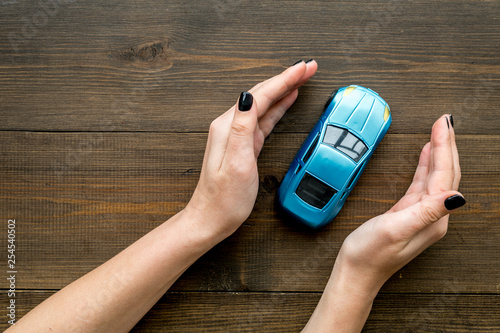 Car insurance concept. Safety of auto. Car toy in female hands on dark wooden background top view space for text