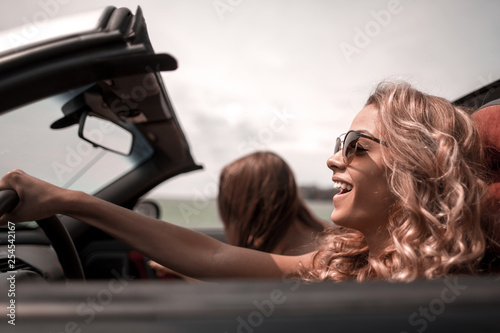 close up. fashionable blonde driving a convertible - 254542167