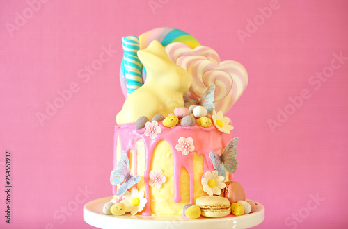 Poster Confiserie On-trend Easter theme candy land drip cake decorated with lollipops, candy eggs and white chocolate bunny in party table setting.