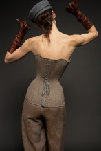Studio Portrait Of Beautiful Woman In Casual Clothes. Young Model Wearing Corset Standing On Grey Background
