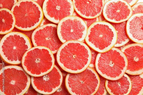 Fotografia Many sliced fresh grapefruits as background, top view