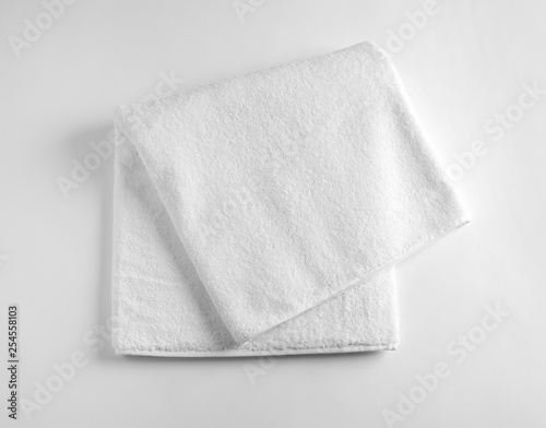 Fotomural Folded soft terry towel on light background, top view