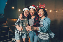 Group Of Young Female People Celebrating Christmas Eve On The Rooftop Of The Building. Cheerful Crazy Women Cheers With Champagne Glasses Outdoor At Night. Ladies Toasting Champagne Enjoy Gathering.