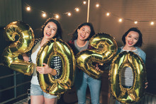 Carefree Ladies Carrying 2020 Gold Number Balloon Showing To Camera On The Rooftop Party. Group Of Young Girls Countdown New Year Eve Together Midnight Outdoor On The Roof. Charming Asian Women Smile