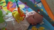 Newborn Baby Playing in its Colorful Baby Gym