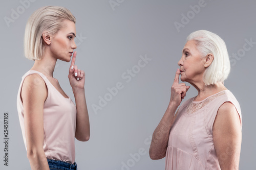 Fotografie, Obraz  Serious short-haired ladies holding their fingers close to mouths