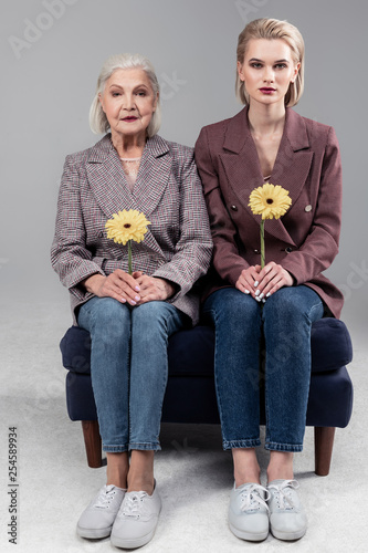 Fotografie, Obraz  Precious good-looking tidy women sitting on little sofa close to each other