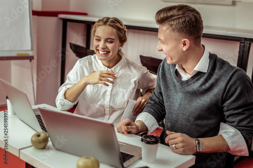 Valokuva  Outgoing co-workers being in great mood at work while laughing
