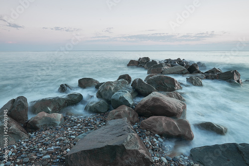Fotografie, Obraz  The sea washes the big rocks against the pink sunset