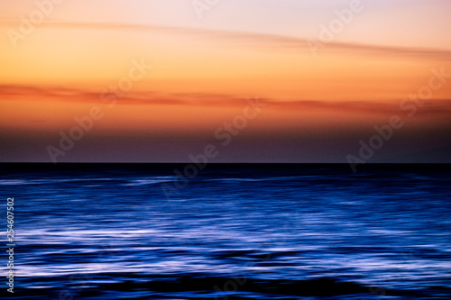 Keuken foto achterwand Rood traf. Water with stretch movement motion effect and coloured sky - sunset time with touristic and vacation concept