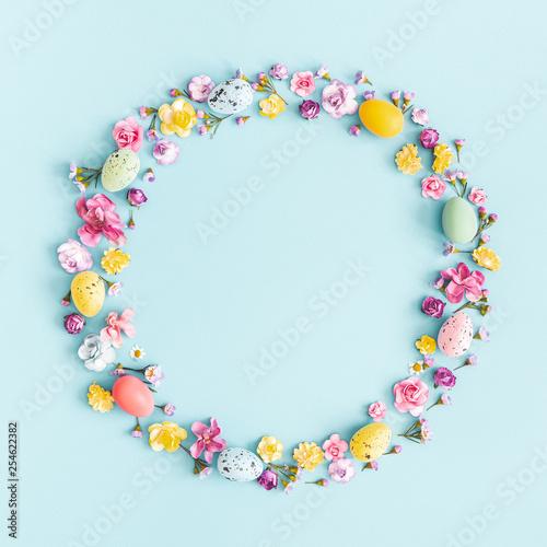 Fototapeta Easter eggs, colorful flowers on pastel blue background