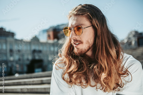Vászonkép  Handsome young man with long curly hair spending time outdoors