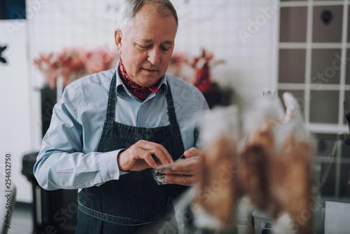 Fototapeta Handsome old gentleman in apron working in cafe obraz na płótnie