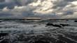 Cloudy sunset deep blue waves crashing on rocky seashore birds and beach