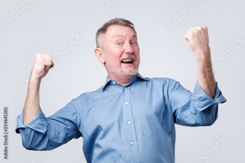 Fotografiet  Happy senior strong man, raising clenched fists in hooray gesture, triumphing