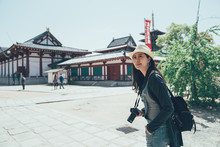 Japan Tourist Female Visiting Attraction Shitennoji Temple Taking Photo Picture At Famous Landmark. Asia Travel Sightseeing Shinto Shrine. Elegant Asian Woman Smiling Carry Camera Looking Around.