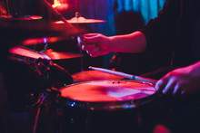 Drummer Playing Drum Set At Concert On Stage. Music Show. Bright Scene Lighting In Club,drum Sticks In Hands.