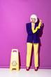 Leinwandbild Motiv Girl in wig standing near wet floor sign and putting on rubber gloves on purple background