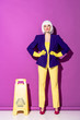 Leinwandbild Motiv Girl in wig and rubber gloves standing with arms akimbo near wet floor sign on purple background