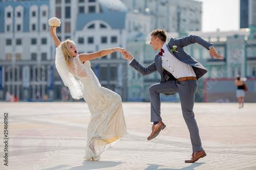 Fotografia bride and groom in wedding attire dancing fiery dance in the town square