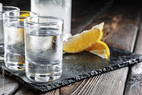 Fotografia Vodka in shot glasses on rustic wood background
