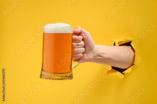 Fotobehang Alcohol Hand holding a beer glass