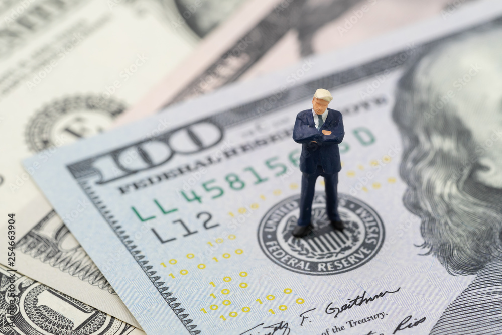 Fototapety, obrazy: Miniature businessman leader standing and thinking on US Federal Reserve emblem on US dollars banknote as FED consider interest rate hike, economics and inflation control