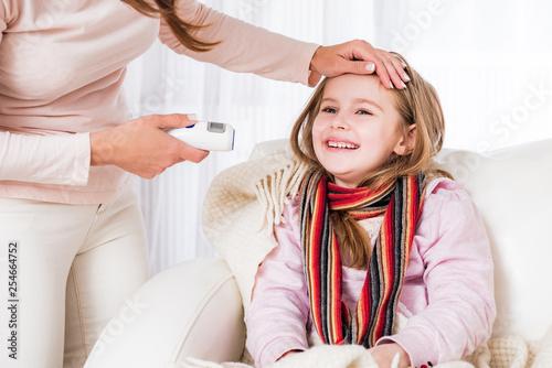 Mum measuring ill smiling daughter's temperature Fototapet