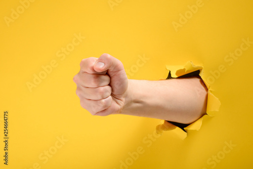 Obraz na plátně Fist punching through yellow paper
