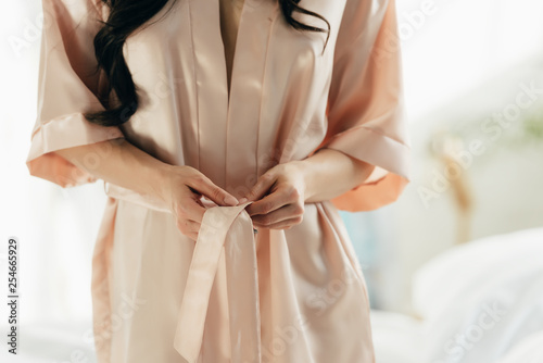 cropped view of woman untying silk robe at home Fototapeta