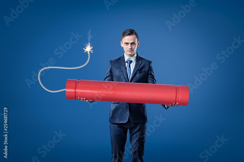 Tela  Young businessman holding big red tnt dynamite stick with lighted fuse on blue b