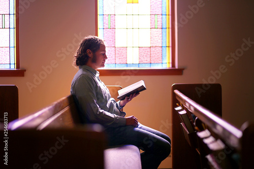 Man Sitting Alone in Dark Empty Church Pew by Bright Stained Glass Window Canvas Print