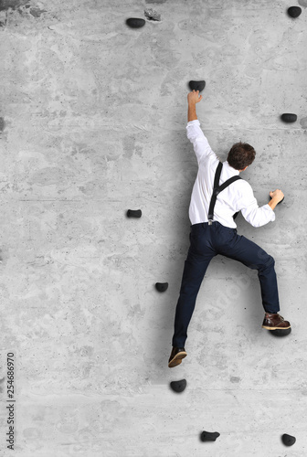 Businessman climbs the wall as a climber, business concept
