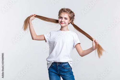 Photo  Cheerful cute girl spreading her long tails and showing their length