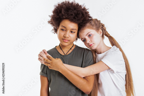 Valokuva  Emotionless pretty long-haired girl hugging her African American friend